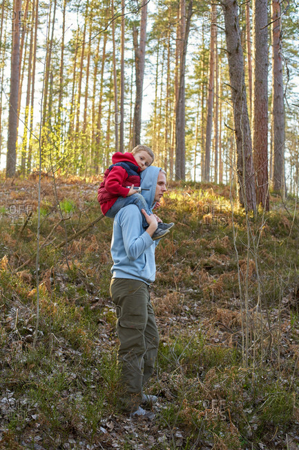 Father holding his son on his shoulders and walking through the forest
