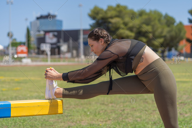 Caucasian attractive woman, wearing sports clothes stretching on the athletic tracks