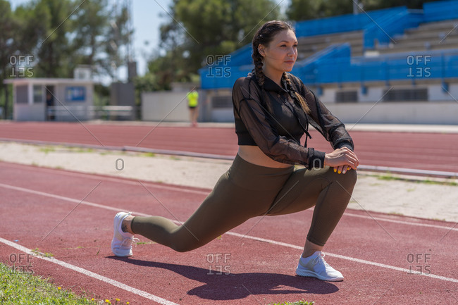 Side view of motivated sporty woman in active wear standing on one leg stretching while looking away