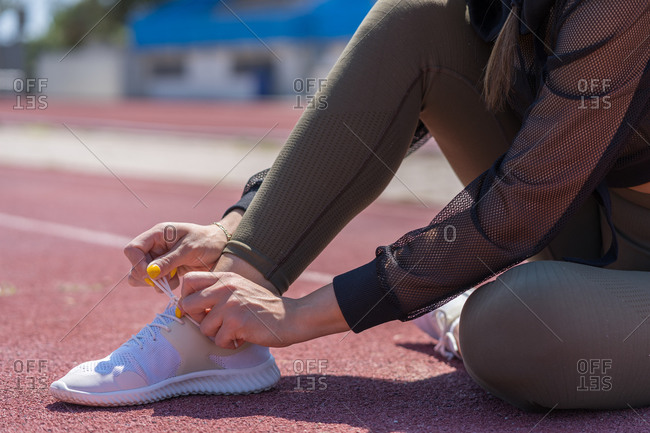 Unrecognizable woman tying her sneakers on athletics tracks to go running