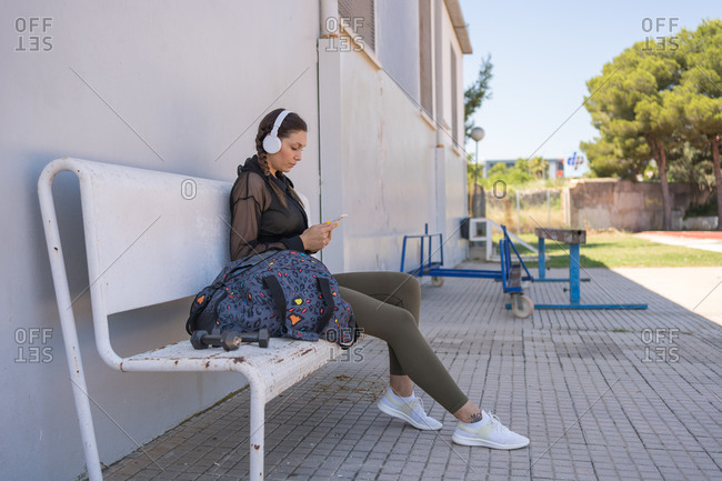 Young runner resting on a wooden bench while checking her mobile phone