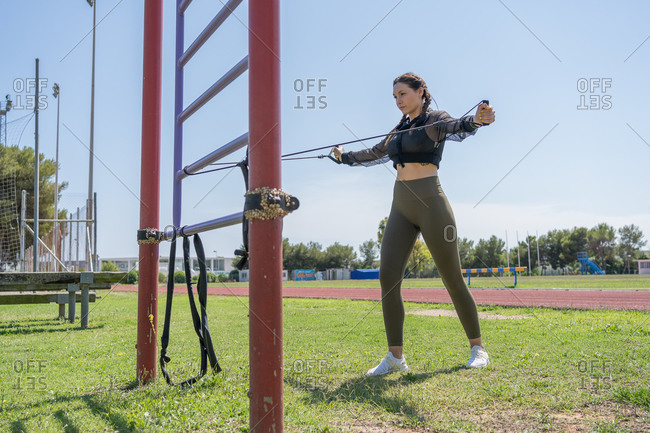 Young woman training with fitness band on the athletic tracks