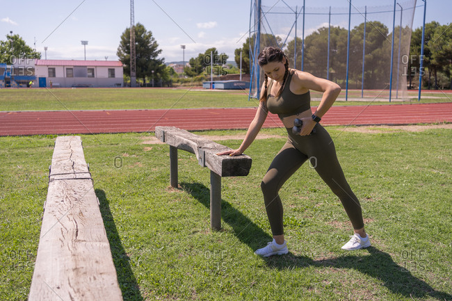 Young woman wearing leggings lifting weights outside