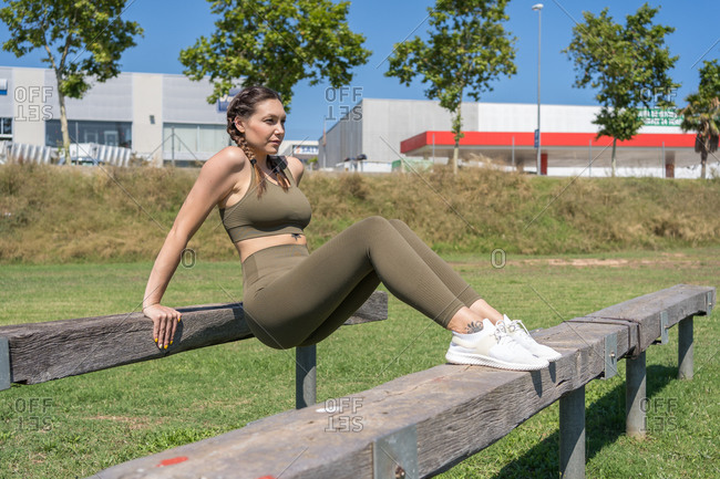 Young woman doing push-ups on a wooden bench