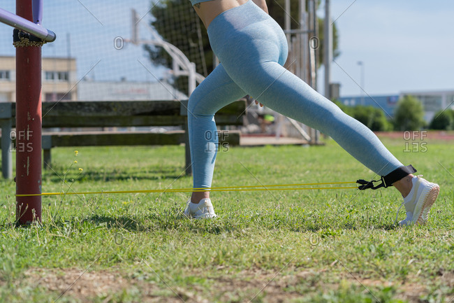 Unrecognizable woman in leggings and top preparing for a run while pulling resistance elastic band on the track