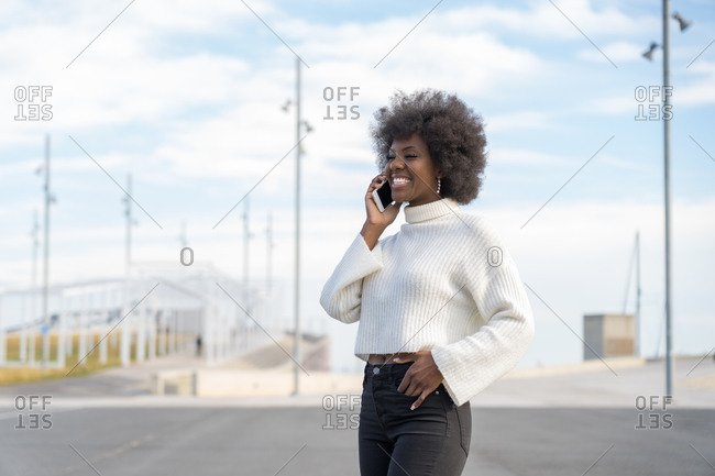 Happy beautiful Afro woman communicating on her cellphone
