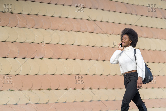 Portrait of a happy African American walking while using her cellphone