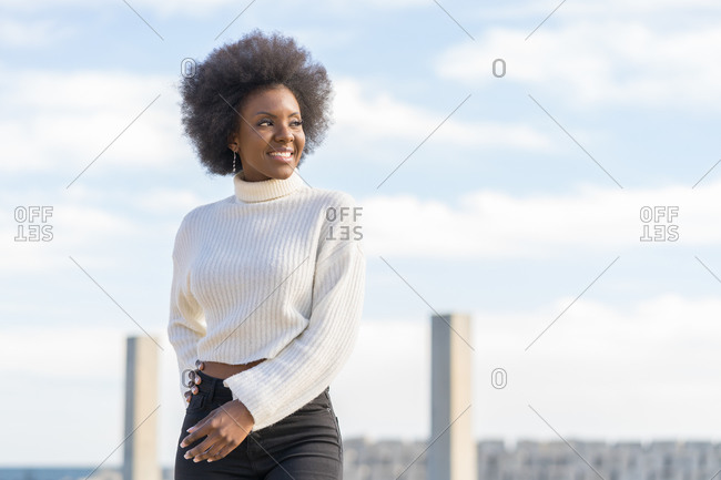 Portrait of a smiling female Afro-American woman- hand in hair