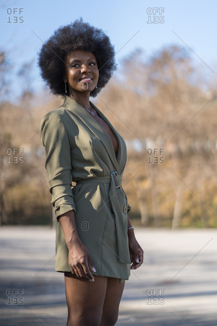Portrait of young woman with afro hairdo standing on a street in the city