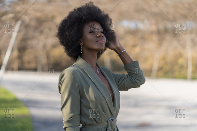 Portrait of young woman wearing green dress with afro hairdo