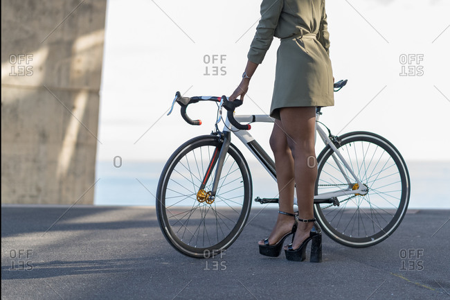 Portrait of an unrecognizable woman in a green dress and high heels posing with a road bike