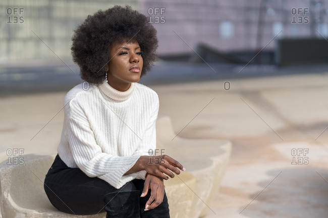 Serious woman with a natural afro hairstyle looking away sitting on a stone bench
