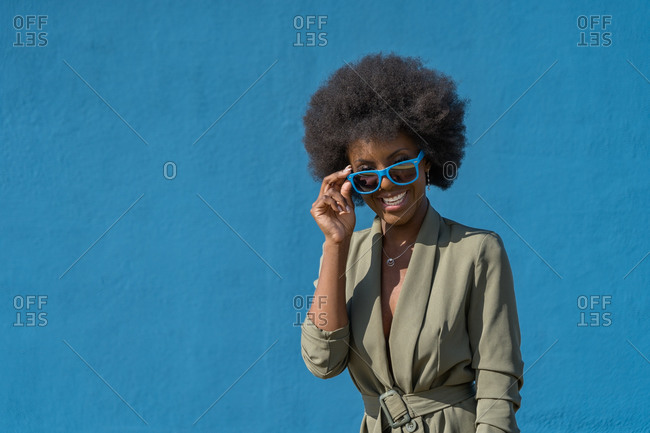Modern young African American woman with afro hairstyle wearing green dress with sunglasses standing on blue background