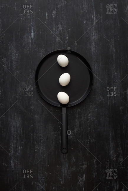 Natural farm chicken eggs on a black pan for cooking healthy breakfast on a black stone background, copy space. Top view. Healthy natural food.