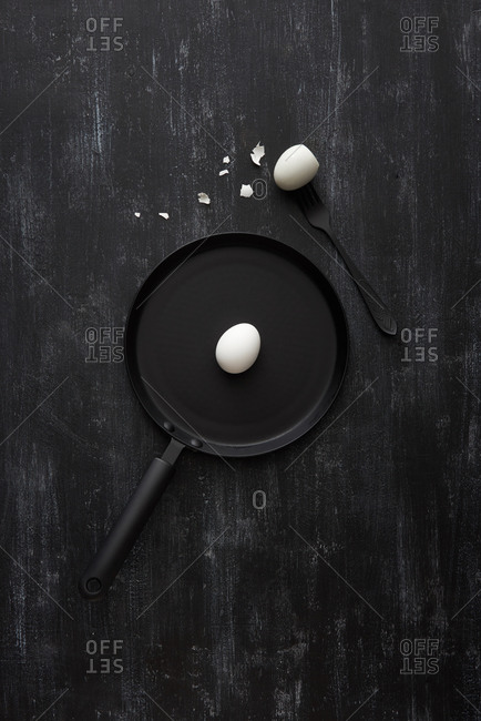 Black pan with prepared healthy breakfast from boiled eggs on a black stone background, copy space. Healthy natural food. Top view.