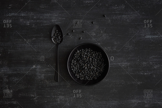 Healthy organic vegan food - natural organic kidney beans in a ceramic bowl on a dark stone background, copy space. Top view. Vegan food concept.