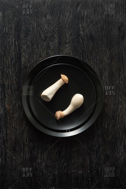 Fresh natural organic mushroom Pleurotus eryngii in a black ceramic plate on a dark stone background, copy space. Vegan healthy food.