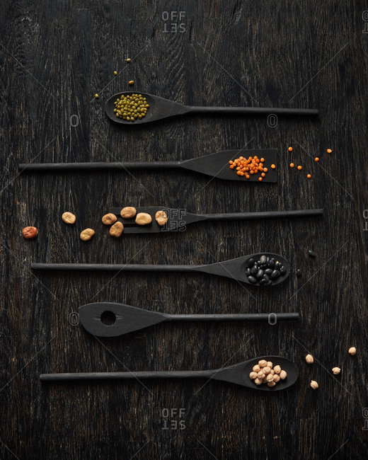 Assortment of different natural organic legumes on black wooden spoons on a dark wooden background, copy space. Top view. Healthy vegan food.