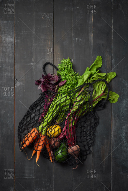 Freshly picked natural organic vegetables - carrot, beet, lemon and avocado in an eco friendly net bag on a dark wooden background, copy space. Top view. Vegetarian healthy food.