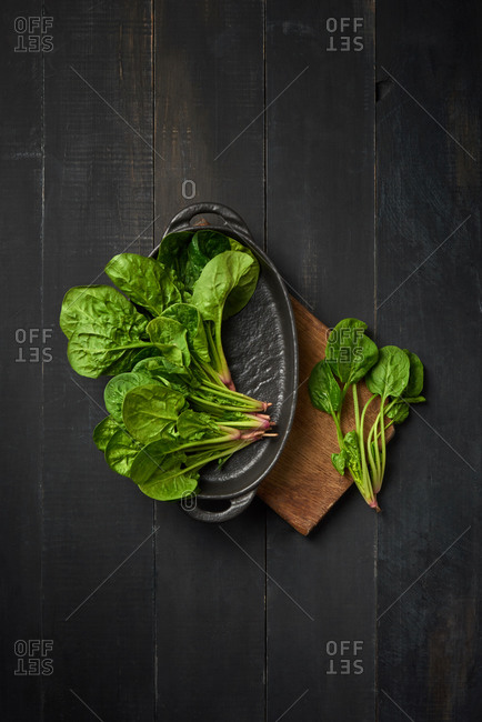 Cast iron pan with home grown fresh natural organic green spinach on a wooden board on a dark wooden background, copy space. Top view. Vegan healthy food.