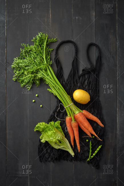 Eco friendly net bag for packaging freshly picked natural organic vegetables - carrot, lettuce and lemon on a dark wooden background, copy space. Top view. Vegetarian healthy food.