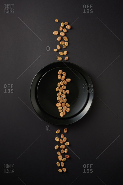 Creative composition from healthy natural beans line on black ceramic plates on the same color background, copy space. Top view. Vegan food concept.