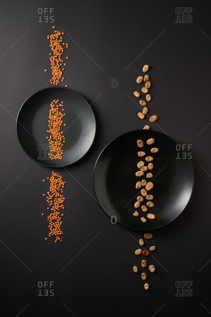 Healthy organic vegetarian food - two lines from natural organic beans and red lentil on two black ceramic plates on the same color background, copy space. Top view. Vegan food concept.
