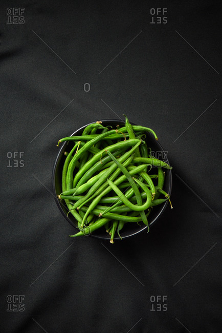 Freshly picked natural organic green bean in a ceramic bowl for cooking healthy vegetarian food on a black textile background, copy space. Top view. Vegan food concept.