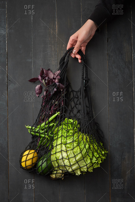 Woman hand holding eco friendly net bag with home grown fresh organic vegetables, greenery and lettuce against dark wooden background, copy space. Vegetarian healthy food.