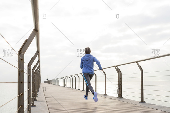 Back view of a fit woman running on a promenade on a cloudy day