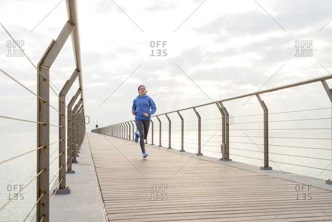 Front view of a fit woman running on a promenade on a cloudy day