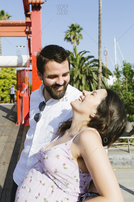 Happy pregnant couple laughter together outdoors