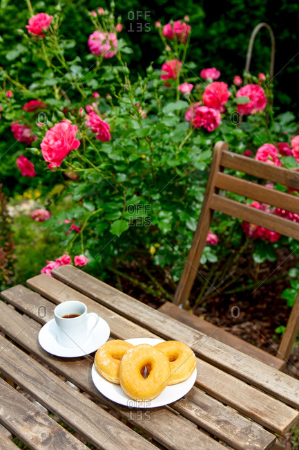 High angle view of espresso coffee and donuts on a wooden table near pink roses in a garden