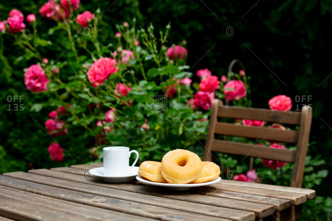 Cup of espresso coffee and donuts on a wooden table near pink roses in a garden
