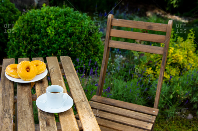 Cup of espresso coffee and donuts on a wooden table near garden