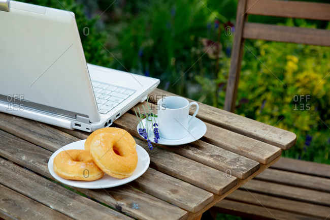 Cup of espresso coffee and computer with donuts on a wooden table near lavender garden