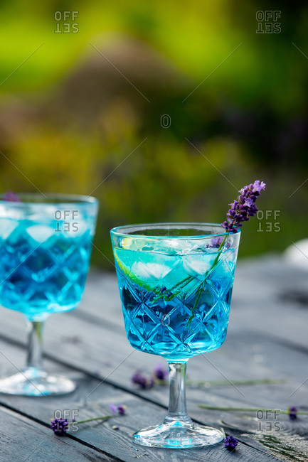Blue cocktail with ice and lavender on a wooden table