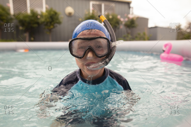 Young boy wearing snorkel and goggles in a swimming pool