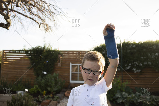 Blonde boy with glasses wearing a raising his arm covered in a blue cast