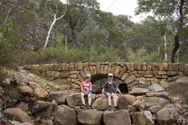 Two boys hiking in front of a rock bridge in the woods