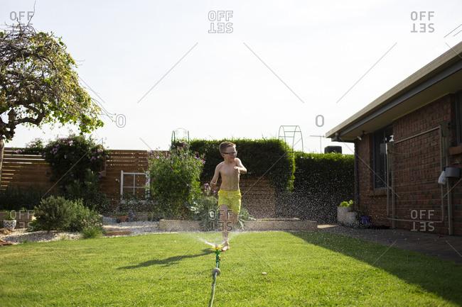 Boy running through a backyard sprinkler