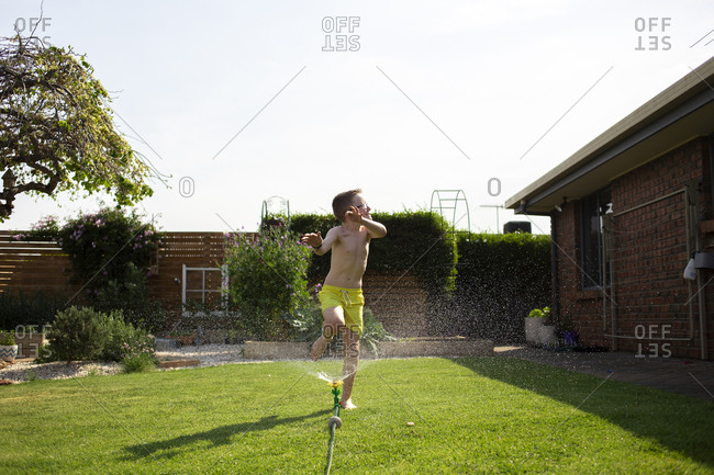 Boy jumping through a backyard sprinkler