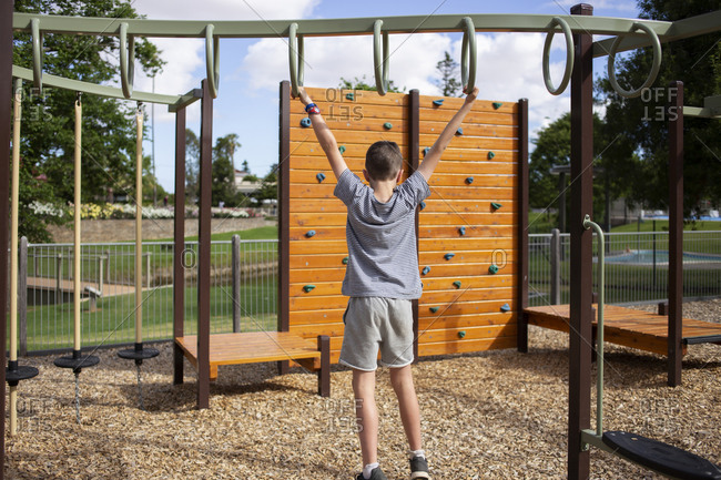 Little boy swinging from monkey bars at a playground