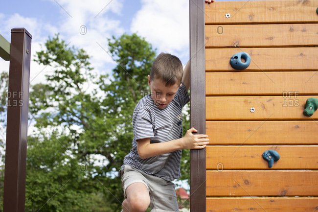 Boy climbing on a wooden climbing wall on a playground