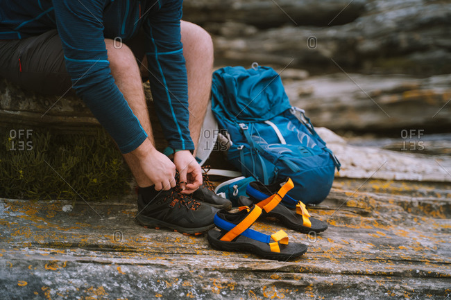 Man unties shoes laces to wear colorful sandals while seated on rocks