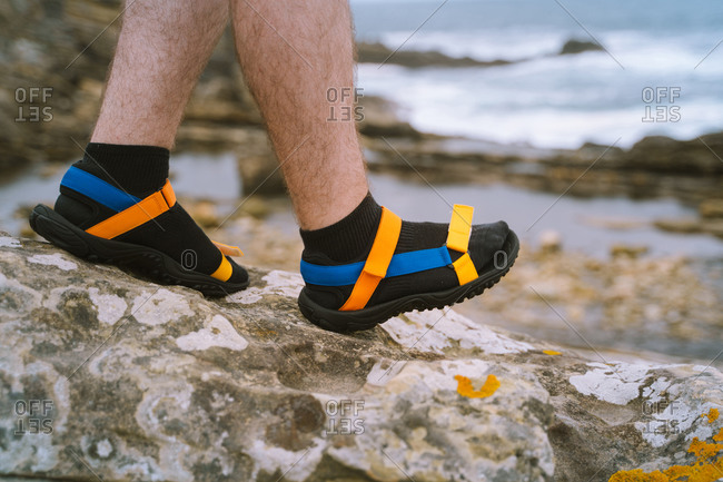 Hairy legs wearing colorful sandals with black socks