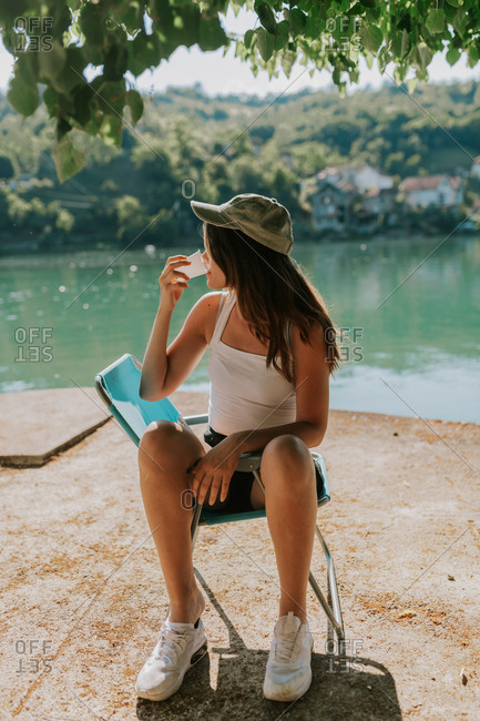 Young woman sitting in blue chair drinking from plastic cup at Lake Jablanica in Bosnia and Herzegovina