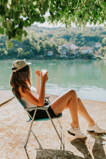 Young woman sitting in blue chair looking out at Lake Jablanica in Bosnia and Herzegovina