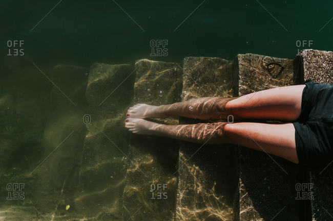 Feet of a young woman sunbathing on steps by Lake Jablanica in Bosnia and Herzegovina