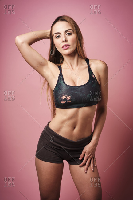 Blonde fitness girl wearing sport clothes while touching her long hair and looking at camera on a pink background